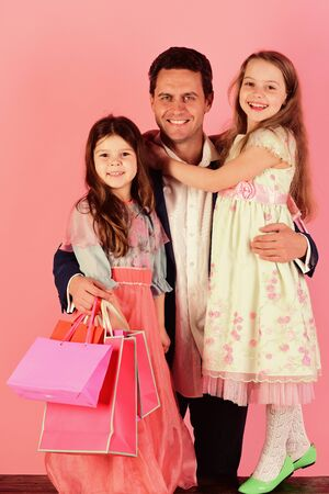 Schoolgirls in dresses and father hold packets. Shopping and presents