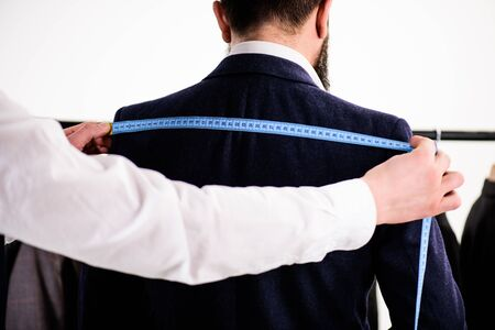 Tailors hands measure back for sewing suit, white background. Stok Fotoğraf