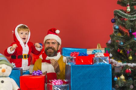 Santa Claus and little santa or elf with gift boxes Stock Photo