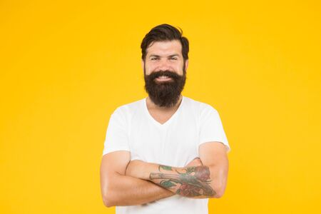 happy brutal bearded man on yellow background. handsome confident man has perfect hairstyle. male facial care. portrait of brutal bearded man. thinking stylish man smiling