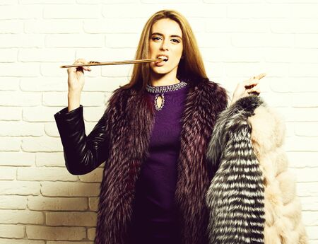 serious fashionable woman in fur on white brick wall background