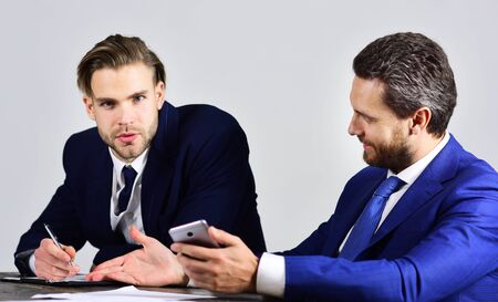 Business people hold smartphone, pen and notebook.