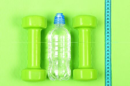 Two plastic dumbbells and bottle. Dieting and bodybuilding concept. Set of hand weights on bright background. Pair of green fitness dumbbells, centimeter and bottle of water on green background.