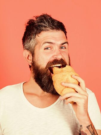 Biting croissant. Delicious breakfast. Man start morning with croissant. Bearded hipster enjoy breakfast. Yummy croissant. Fresh baked croissant. Calories and gluten. Diet and dieting. Bakery concept