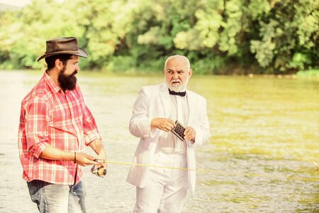 Fishing skills. Fish with companion who help in emergency. Men friends relaxing river background. Personal instructor. Expert fisherman. Bearded man elegant businessman fish together. Learn to fish. Foto de archivo - 150084414