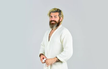 Spa resort. Hotel apartments. Bearded guy wearing white bathrobe. Take steps to improve your sleep habits. Hygiene and spa. Man in bathrobe in bathroom. Mature man wear bathrobe relaxing at spa Standard-Bild