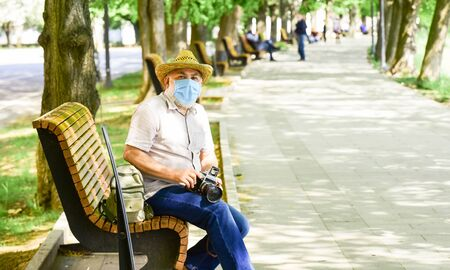Pandemic concept. Professional photographer work during coronavirus quarantine. Risky photographer. Keep working. Tourist use camera take photo. Urban photography. Senior man in respirator mask