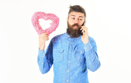 Bearded man holds gift and talks by phone.