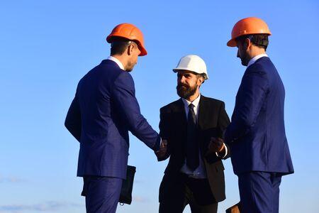 Leaders hold clip folder and shake hands. Фото со стока