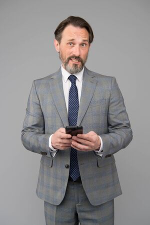 successful businessman deal with problem online. agile business. mature boss with amazed look. man holding device and touching screen. texting to colleague. technology bring success. Own business Reklamní fotografie