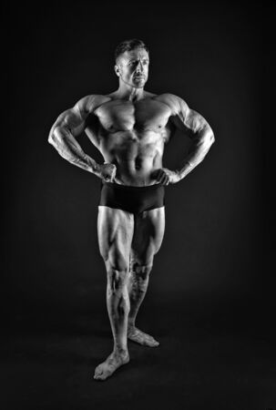 Professional bodybuilder. Bodybuilder black background. Fit bodybuilder show muscular body. Strong bodybuilder with six pack abs. Muscle man. Strength training. Bodybuilding and fitness