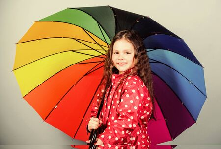 Small girl in raincoat. rain protection. Rainbow. autumn fashion. cheerful hipster child in positive mood. happy small girl with colorful umbrella. Waiting for inspiration