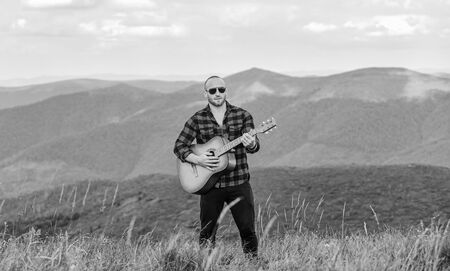 Music for soul. Playing music. Sound of freedom. In unison with nature. Acoustic music. Musician hiker find inspiration in mountains. Keep calm and play guitar. Man with guitar on top of mountain Stock Photo
