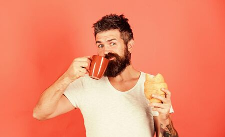Fresh baked croissant. Delicious breakfast. Man start morning with coffee and croissant. Unhealthy but yummy breakfast. Bearded hipster enjoy breakfast drink coffee. Morning tradition concept Banque d'images