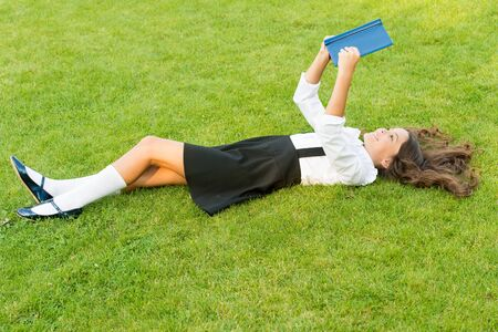 Achieving Excellence. small girl reading book. literature for kids. write childhood memories. her diary. making notes in notebook. back to school. kid study in park. relax on green grass with book