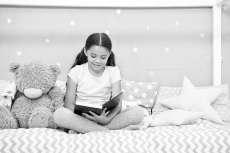 Read to me. Little girl read story to teddy bear. Small kid read book in nursery. Literature and library. Just want nice bedtime read. Child development. Developing imagination through reading Banque d'images