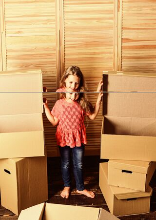 At your service. happy child cardboard box. repair of room. new apartment. happy little girl with bear toy. Cardboard boxes - moving to new house. purchase of new habitation