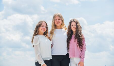 three girls on sky background. concept of female friendship. sisterhood and family. best friends together at school. back to school. happy childhood. cheerful small kids Standard-Bild