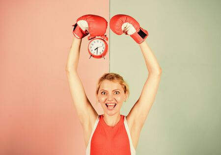 Boxer fighting with alarm clock. Time for boxing training. Punctuality and personal efficiency. Control time. Time management skills. Battle for self discipline. Woman holding clock boxing gloves