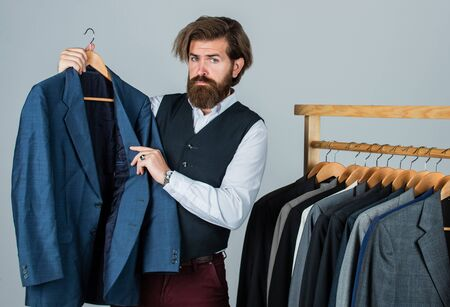 Man in custom tailored suit presenting tailored tuxedo. Man clothing in boutique. tailor in his workshop. Handsome bearded fashion man in classical costume suit. Looking for design inspiration Foto de archivo - 149932748