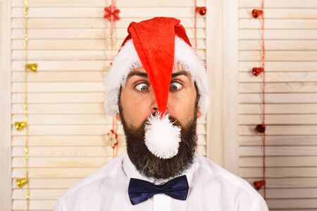 Santa Claus in red hat with grimace on face. Man with beard and bow tie looks at pompon in front of his eyes. Guy on wooden wall background, defocused. Celebration and New Year mood concept