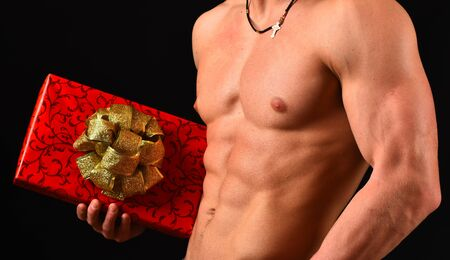 Sports, holidays and surprise concept. Guys abs and strong chest. Athletes body in close up, hand holding red gift box with golden bow for Christmas. Male with naked torso isolated on black background Stock Photo