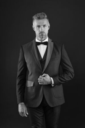 Appreciate classics. Bearded man with formal look. Hipster black background. Brutal man in tuxedo suit. Classic can make man look smarter. Black tie. Fashion shop. Buy clothes. Menswear concept