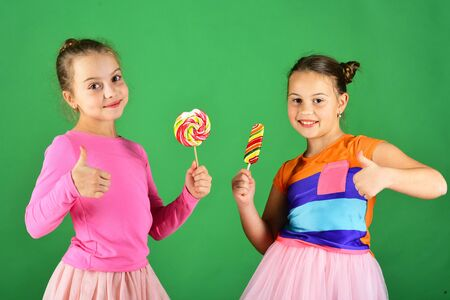 Girls eat big colorful sweet caramels. Confectionery and childhood Archivio Fotografico