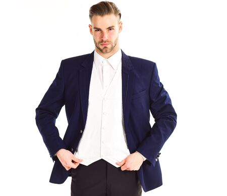 Man in suit with nice hairstyle correcting his vest.