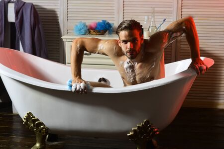 Guy with beard and seductive face in bathtub