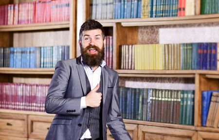 Bearded man in elegant suit smiles and shows thumb up.