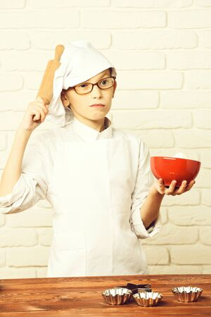 serious boy cute cook chef on brick wall background