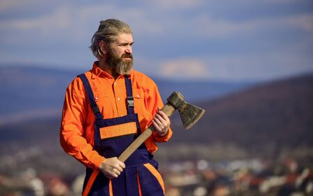 bearded man in uniform. mature man builder use axe. professional repairman working with ax tool. build and construction. Skilled architect repair and fix. engineer career