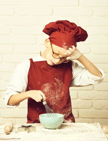 stained cute cook chef boy on white brick wall background