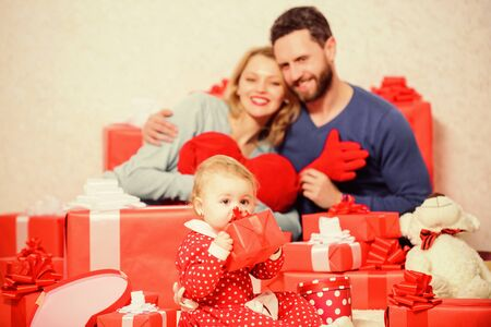 Romantic mood. Shopping. Boxing day. Happy family with present box. Love and trust in family. Bearded man and woman with little girl. Valentines day. Red boxes. father, mother and doughter child