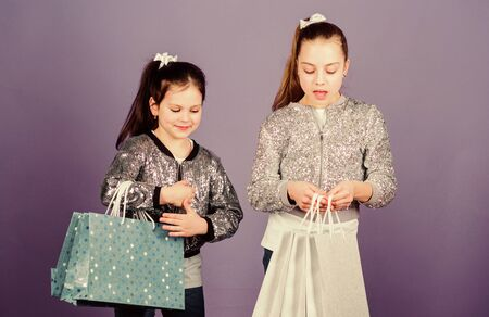 Black friday. Girls sisters friends with shopping bags violet background. Shopping day. Children bunch packages. Kids fashion. Discover something new. Shopping and purchase. Sale and discount