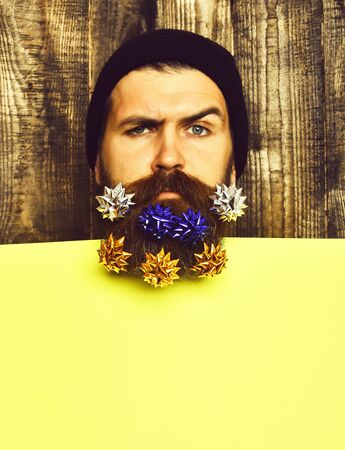Bearded man, brutal caucasian squinting hipster with gift decoration stars Banco de Imagens