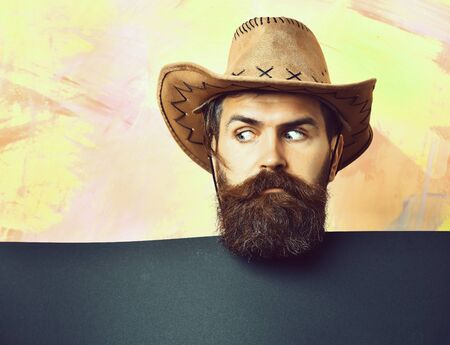 Bearded brutal caucasian hipster cowboy on colorful background