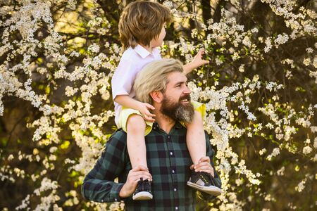 Spring walk. Simple happiness. Happy family. Fatherhood happiness. Fathers day. Little boy and father in nature background. Hipster and baby son. Exploring garden together. Happiness concept