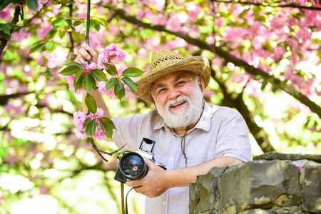 Retirement travel. Enjoying free time. Travel and tourism. Capturing beauty. Happy grandfather. Spring holidays. Travel photo. Photographer in blooming garden. Senior man hold professional camera
