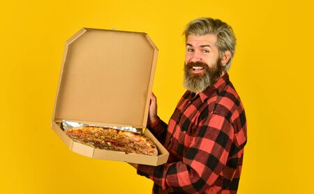 Hungry man going to eat pizza alone. Fresh and hot. In mood for Italian food. Man bearded hipster hold cardboard pizza box. Pizza delivery service. Send meals to homes. Delivering food to apartment Zdjęcie Seryjne