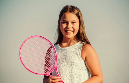 Child play tennis blue sky background. Sporty kid. Small girl with pink tennis racket. Summer leisure. Sport game. Playful cheerful kid. Happy childhood. Positive. Emotional baby. Active life Zdjęcie Seryjne
