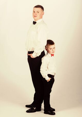 Grow up gentleman. Dad and boy white shirts with bow ties. Gentleman upbringing. Little son following fathers example of noble man. Gentleman upbringing. Father and son formal clothes outfit