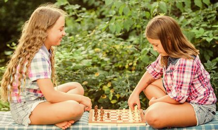 spend time together. family time. two concentrated girls play chess. chess playing sisters. skilled children. turn on your brain. make the brain work. early childhood development. worthy opponents Фото со стока - 150297686