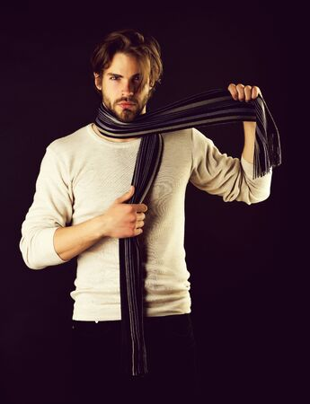 Serious guy with beard and moustache takes striped scarf