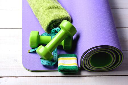 Barbells near cyan measuring tape lie on purple yoga mat. Shaping and fitness equipment. Dumbbells in green color, hand band, twisted tape and towel on light wood background. Workout and sport concept