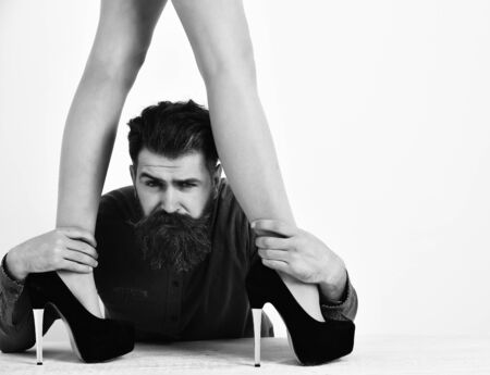 bearded man with sexy female legs has serious face Banco de Imagens