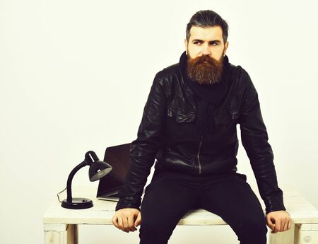 Bearded brutal caucasian hipster sitting on table with laptop on