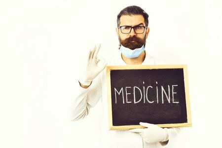 Bearded caucasian doctor holding syringe and board with Medicine inscription Banco de Imagens