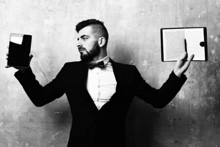 Business director with beard holds tablet and blank open organizer